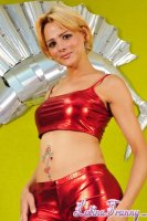 Gabriele. Short blonde hairy Brazilian shemale Gabriele in a red latex outfit posing